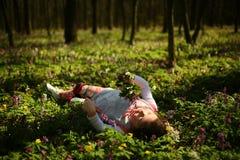 Mała dziewczynka kłaść na zieleni ziemi Obrazy Royalty Free