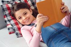 Mała dziewczynka kłama mienie książkową przyglądającą kamerę szczęśliwą w domu Obraz Stock