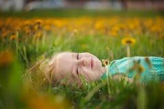 Mała dziewczynka kłama na trawie w kwiat polanie w lecie zdjęcie royalty free
