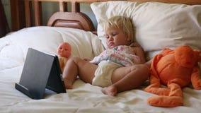 mała dziewczynka kłama w łóżku wśród zabawek i ogląda kreskówki zbiory