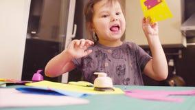 Mała dziewczynka klei barwiącego papier i ciie zbiory