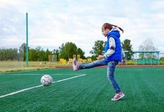 Mała dziewczynka kopie piłkę na boisku piłkarskim fotografia stock
