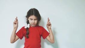 Mała dziewczynka krzyżuje palce spełniać ona sen dziewczyna krzyżuje nad białym tłem z ona palce balerina trochę zbiory wideo