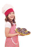 Mała dziewczynka kucharz z czekoladowymi donuts Obrazy Royalty Free