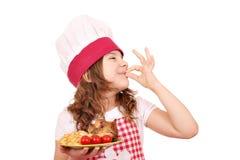 Mała dziewczynka kucharz z kurczaków skrzydłami i ok ręka podpisujemy Obraz Stock