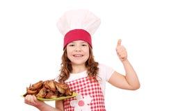 Mała dziewczynka kucharz z kurczaków skrzydłami up kciukiem i Obraz Stock
