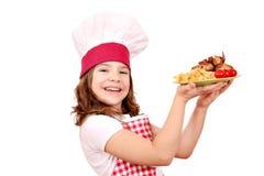 Mała dziewczynka kucharz z piec kurczaków skrzydłami na talerzu Zdjęcie Stock