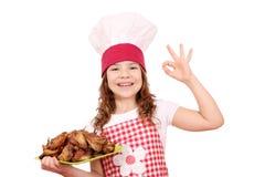 Mała dziewczynka kucharz z piec kurczaków skrzydłami si ok ręką i Zdjęcia Stock