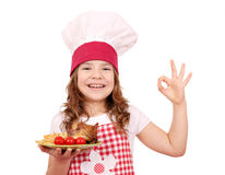 Mała dziewczynka kucharz z piec kurczaków skrzydłami si ok ręką i Zdjęcia Royalty Free