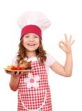Mała dziewczynka kucharz z piec kurczaków skrzydłami si ok ręką i Obraz Stock