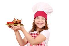 Mała dziewczynka kucharz z piec na grillu kurczaków skrzydłami Zdjęcia Royalty Free