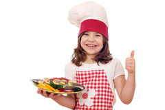 Mała dziewczynka kucharz z przygotowanym pstrąg up i kciukiem Zdjęcie Stock