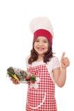Mała dziewczynka kucharz z pstrąg ryba up kciukiem i Zdjęcia Royalty Free
