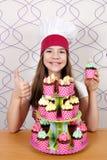 Mała dziewczynka kucharz z słodkimi muffins deser up i kciuk Obrazy Stock