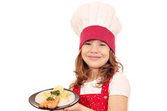 Mała dziewczynka kucharza chwyta naczynie z łososiowym owoce morza Fotografia Stock