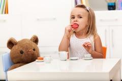 Mała dziewczynka ma herbacianego przyjęcia z jej zabawkarskim niedźwiedziem Zdjęcie Royalty Free