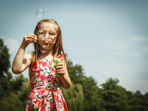 Mała dziewczynka ma zabawę dmucha mydlanych bąble w parku Obrazy Royalty Free