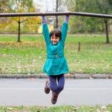 Mała dziewczynka ma zabawę na boisko gimnastyk barze Zdjęcia Stock