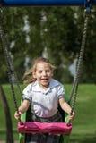 Mała Dziewczynka Ma zabawę na huśtawce w Zielonym parku fotografia stock