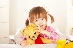 Mała dziewczynka ma zabawę z mokietu niedźwiedzia zabawką Obrazy Stock