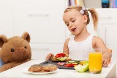 Mała dziewczynka ma zdrowego przekąski obsiadanie przy stołem z ona Zdjęcia Royalty Free