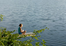 Mała dziewczynka medytuje jeziorem Obraz Royalty Free