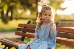 Mała dziewczynka model w błękita słońca i sukni szkłach siedzi na ławce w parku obrazy stock
