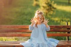 Mała dziewczynka model w błękita słońca i sukni szkłach siedzi na ławce w parku zdjęcie royalty free