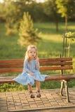 Mała dziewczynka model w błękita słońca i sukni szkłach siedzi na ławce w parku obraz royalty free