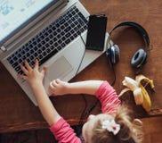 Mała dziewczynka naciska klawiaturę jego laptop Zdjęcie Stock