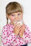 Mała dziewczynka napojów mleko korzyści mleko i wapnie dla dzieci, Dziecko trzy roku obraz stock