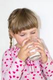Mała dziewczynka napojów mleko korzyści mleko i wapnie dla dzieci, Dziecko trzy roku fotografia royalty free