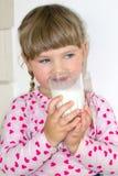 Mała dziewczynka napojów mleko korzyści mleko i wapnie dla dzieci, Dziecko trzy roku obrazy stock