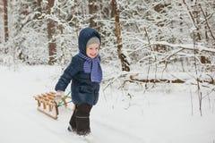 Mała dziewczynka niesie saneczki na mroźnym zimnym zima dniu Zdjęcia Royalty Free