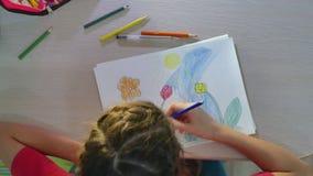 Mała dziewczynka obrazu farba przy stołem uczennicy dziewczyny nastolatek remisy rysuje z ołówkami indoors Zdjęcie Stock