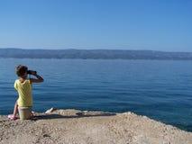 Mała dziewczynka ogląda morze z lornetkami zdjęcia stock