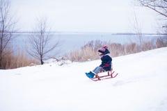 Mała dziewczynka ono ślizga się w dół od śnieżnego wzgórza z jej ojcem zdjęcia stock