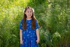 Mała Dziewczynka ono Uśmiecha się przed polem z kwiatami w błękit sukni zdjęcie royalty free