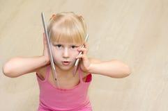 Mała dziewczynka opowiada na telefonie komórkowym i pastylce w różowej sukni Zdjęcia Royalty Free
