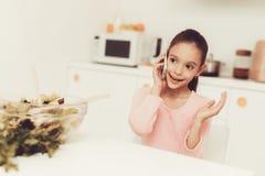 Mała Dziewczynka Opowiada Na telefonie Przy kuchnią fotografia stock