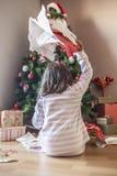 Mała dziewczynka otwiera ich prezenty pod choinką Obraz Stock
