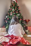 Mała dziewczynka otwiera ich prezenty pod choinką Zdjęcie Royalty Free
