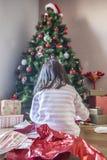 Mała dziewczynka otwiera jej prezenty pod choinką Obrazy Stock
