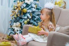 Mała dziewczynka otwiera prezent w żywym pokoju w domu Zdjęcie Royalty Free