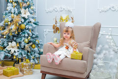 Mała dziewczynka otwiera prezent w żywym pokoju w domu Fotografia Royalty Free