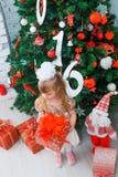 Mała dziewczynka otwiera prezent w żywym pokoju w domu Fotografia Stock