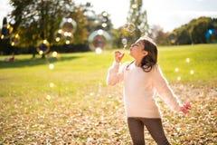 Mała dziewczynka outdoors przy pięknym jesień dniem dmucha mydlanych bąble zdjęcie stock