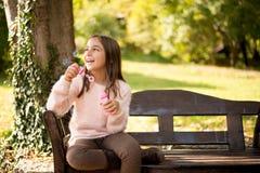 Mała dziewczynka outdoors przy pięknym jesień dniem dmucha mydlanych bąble Obrazy Royalty Free
