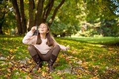 Mała dziewczynka outdoors przy pięknym jesień dniem dmucha mydlanych bąble Obraz Royalty Free
