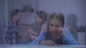 Mała dziewczynka płacz za dżdżystym okno, cierpienie od rodziców koliduje, rodzina zbiory